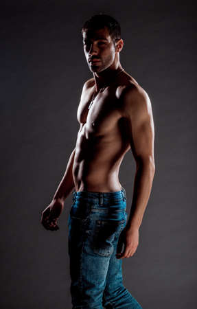 Stylish young man wearing blue denim pants posing half naked Stock Photo