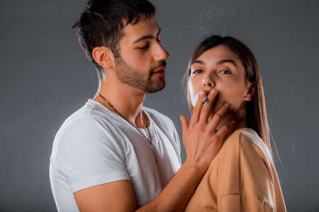 Portrait of sexy young male and female models posing with a cigarette