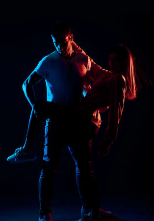 Attractive young man and woman posing against a black background