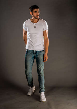 Cool handsome guy wearing stylish blue jeans, white t-shirt and sneakers