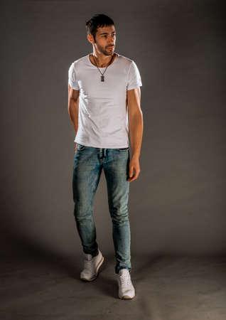 Cooler gutaussehender Kerl mit stylischen Blue Jeans, weißem T-Shirt und Turnschuhen