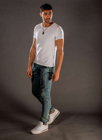 Trendy handsome man posing in blue denim pants, white top and sport shoes