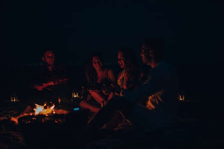 Portrait of young people sitting near campfire on the beach at summer night
