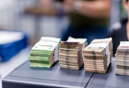 Bundles of different types of cash divided with currency bands and sorted in groups