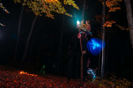 Sorcerer (magician) casting a spell while standing in the magical woods. Holding his magical staff. Magic illumination. Autumn holiday celebration. Mystery and nightmare concept