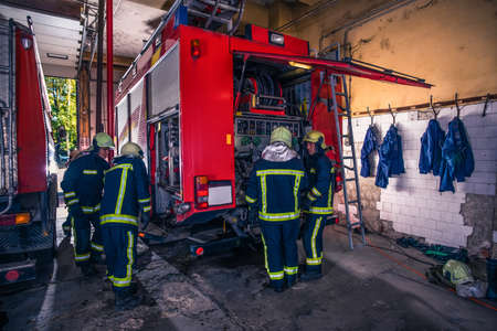 Group of firefighters preparing and inspecting pressure and water in the fire truck inside the fire station