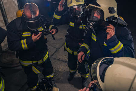 Group of firefighters standing inside the fire brigade wearing helmet and protective uniform