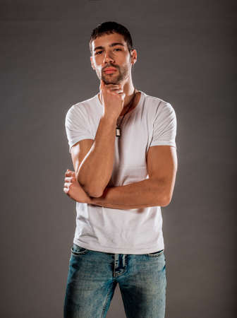 Studio fashion portrait of a young man wearing blue jeans, and white top Stock Photo