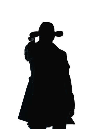 Attractive guy wearing trench coat and a hat, pointing his gun Stock Photo