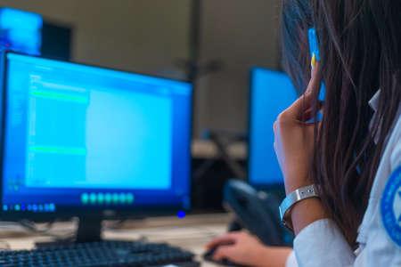 Opérateur de centre de données de sécurité regardant le moniteur tout en parlant au téléphone. Gros plan photo.