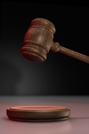 Judges gavel up illuminated with red light on black background photo