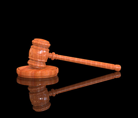 Judges wooden gavel on black floor with reflection