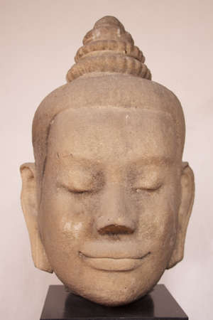 head of smiling buddha made by stone photo