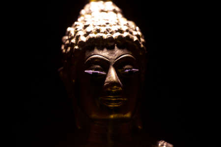 black metal buddha statue placed in dark room with little light photo