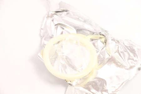 unpacked translucent condom on white background photo