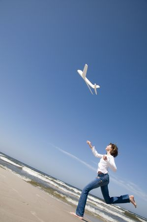 Teenage girl playing with plane model on the beach photo