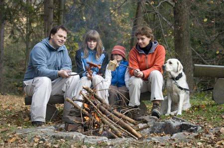 campfires: Happy family with dog near campfire Stock Photo