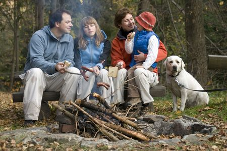 Happy family with dog near campfire Stock Photo