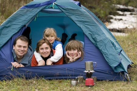 Happy family camping in tent photo