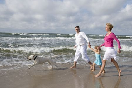 seasides: Happy family playing on the beach Stock Photo