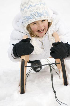Happy girl playing on sledge