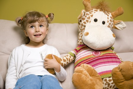 Cute girl with friend - toy on sofa