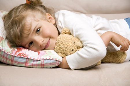 stuffed animals: Little girl with teddy bear on sofa