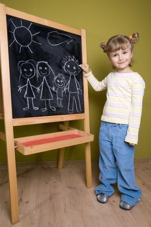 Little girl drawing family at blackboard