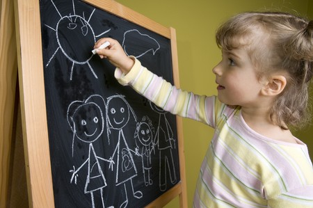 Little girl drawing family at blackboard
