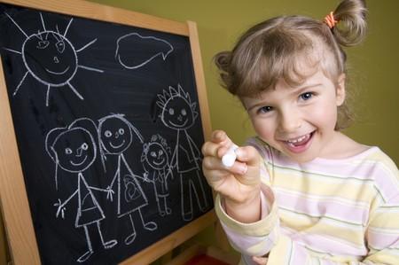 Cute girl drawing family at blackboard photo