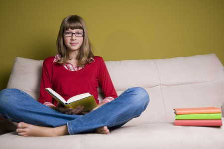 Teenage girl relaxing with book on a sofa