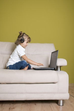 Cute girl with laptop on sofa