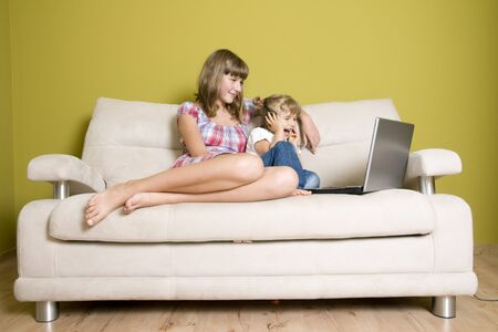 Sisters with laptop on sofa photo