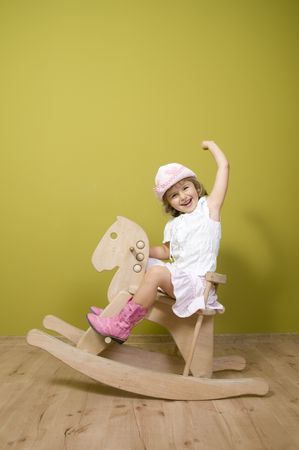 Little country girl playing with rocking horse photo