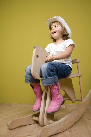 Little country girl playing with rocking horse