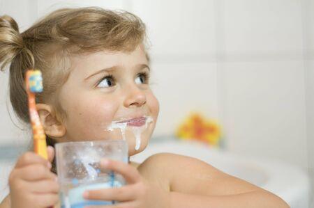 cepillarse los dientes: Ni�a cepillarse los dientes en el cuarto de ba�o