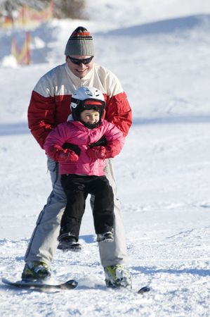 Father and daughter skiing together on mountain photo