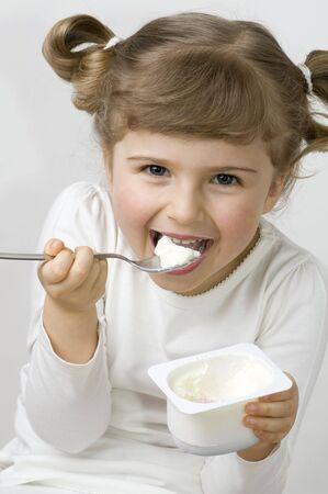 Cute girl eating yogurt Stock Photo
