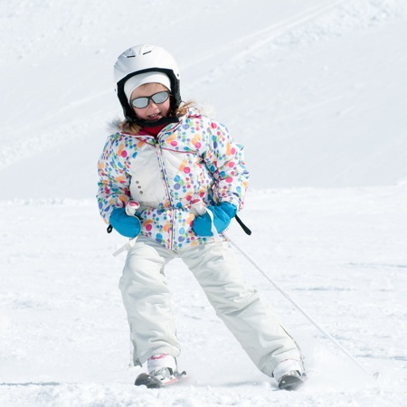 Little girl skiing downhill photo