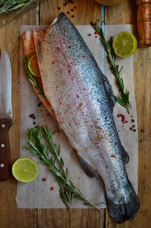 spicery: Eviscerated fresh trout with lime, rosemary and spicery on the preparation table