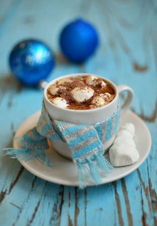 cordially: A cup of marshmallow coffee on the blue wooden table