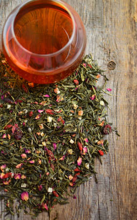 sencha tea: Green tea with the pieces of different fruits and flowers on the wooden table