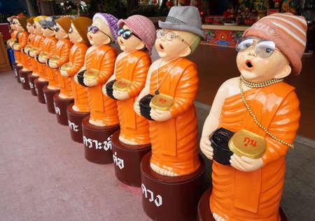 limosna: Ni�o estatua del monje llevar un anteojos. �l sostiene cuenco de las limosnas