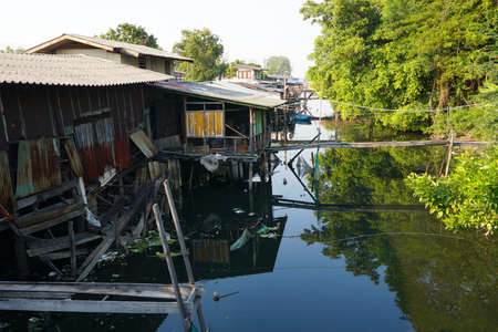 underdeveloped: House on stilts. Views of the citys Slums from the river in Bangkok, Thailand.