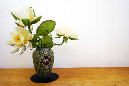 home accent: White flowers in vase on wooden table Stock Photo