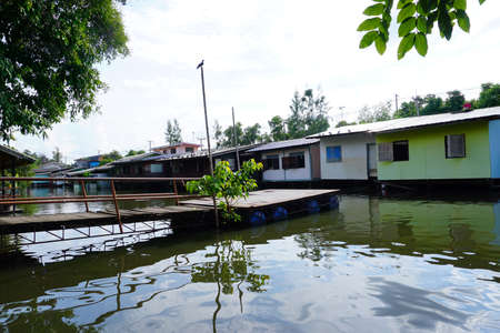 unfortunate: House on stilts. Views of the citys Slums from the river in Bangkok, Thailand.