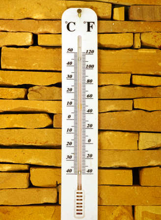 weather gauge: Thermometer in brick background Stock Photo