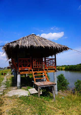 a house with a straw: Straw house near small lake with blue sky in the countryside of Thailand