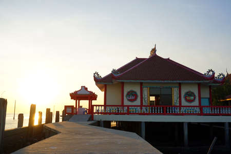 Traditional Chinese temple building next to the ocean with sunset. Located in Samutprakarn , Thailand