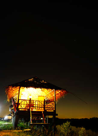 Straw house near small lake with sky in nightime, countryside of Thailand Banco de Imagens